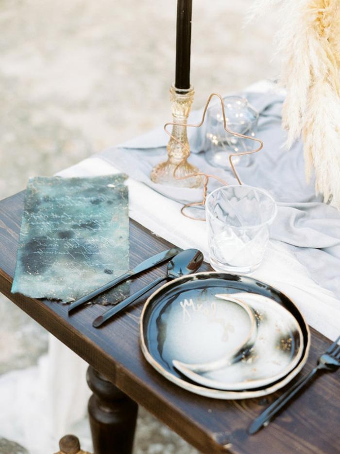 table en bois foncé, assiettes artisanales, bougeoirs en cristal jaune, bougie noire, ustensiles noires