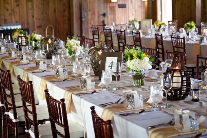 table de mariage blanche, serviettes de tissu beiges, grand bougeoir en bois, mur en bois