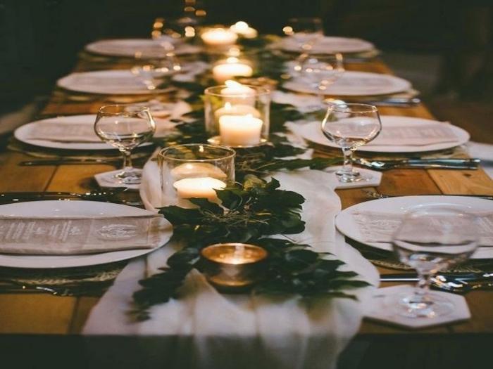 decoration table de mariage, assiettes blanches, chemin de table blanc, branches vertes et porte bougies en verre