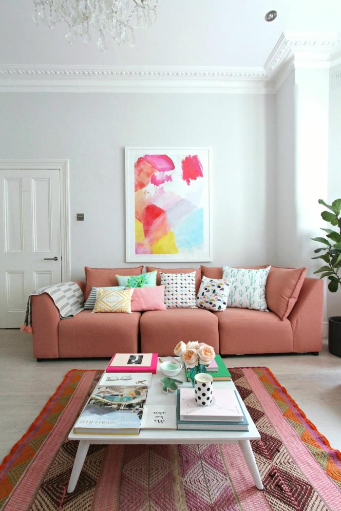 grand sofa couleur saumon, tapis ethnique, table blanche, plafonnier pampille, plante décorative, tableau peinture abstraite