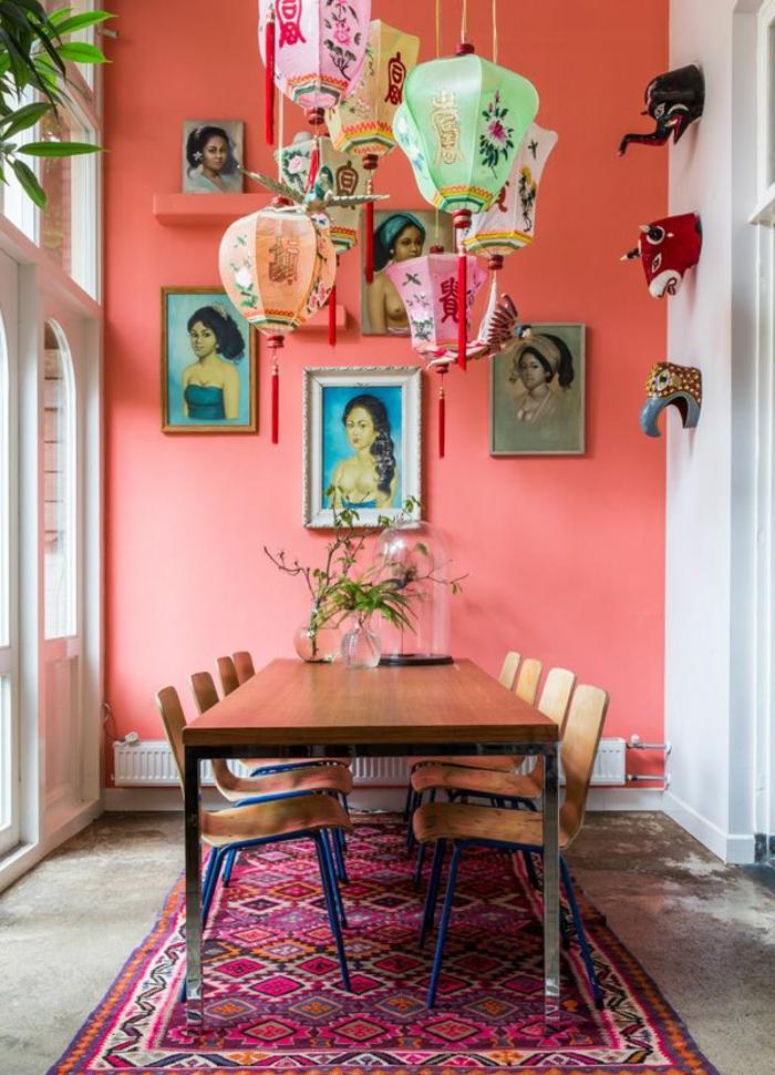 mur en couleur pantone année 2019, grande table à manger, lanternes japonaises suspendues, tapis ethnique pourpre, plusieurs portraits accrochés au mur