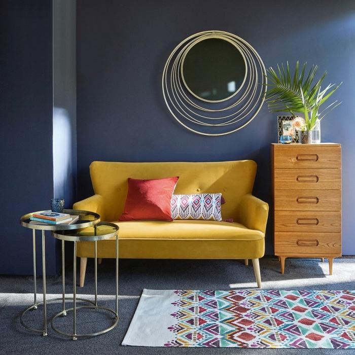 modèle de canapé jaune moutarde décoré de coussins, exemple de table café ronde avec 2 plateaux en métal et verre
