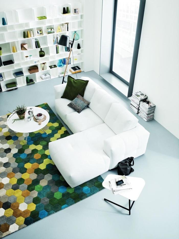 aménagement salon au plafond haut blanc avec meubles bois blanc et canapé d'angle blanc, coussin de couleur vert sapin