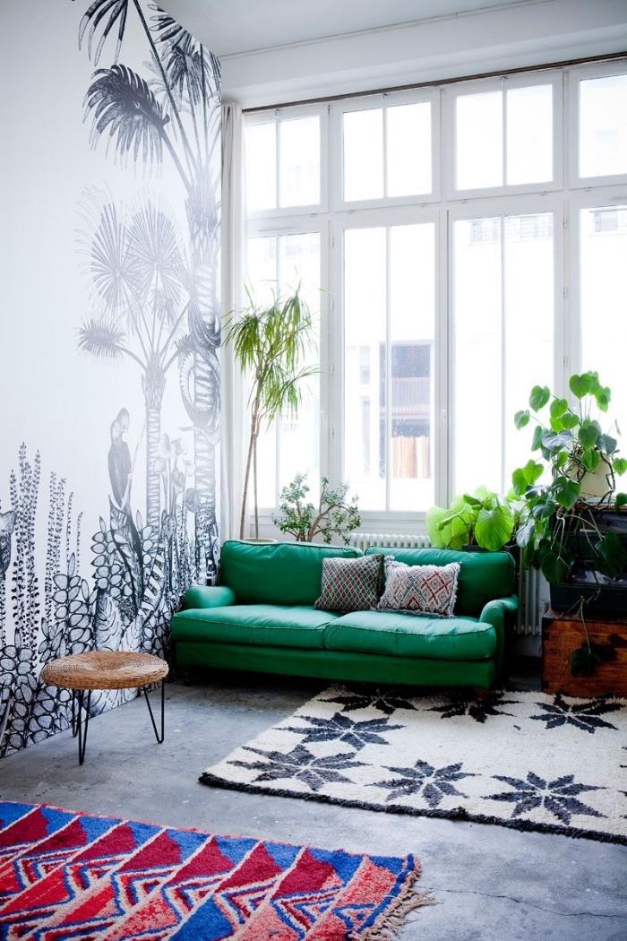 modèle de canapé salon de couleur vert emeraude décoré avec coussins gris, revêtement mural en papier peint blanc et noir