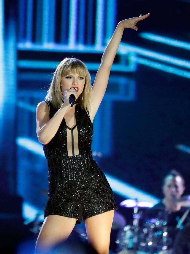 Taylor Swift performance pour le nouvel an sur netflix, salopette courte stylée noir et brillant, chanteuse sur la scène