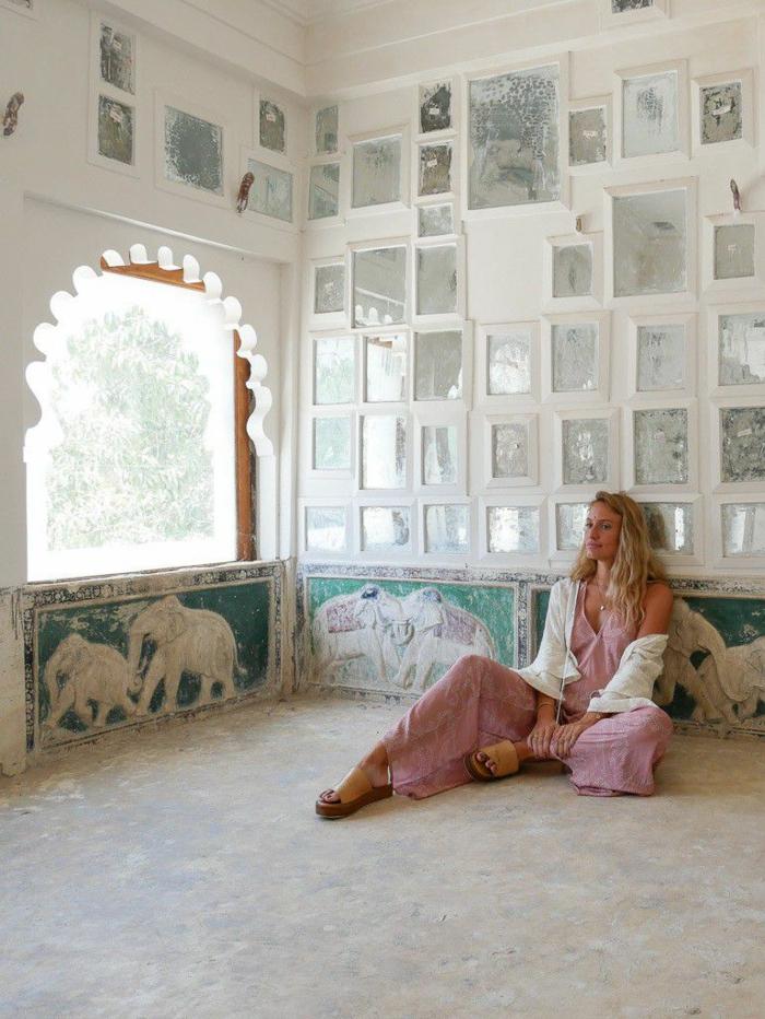 Robe longue bohème chic, femme en robe rose et gilet blanche, intérieur oriental avec éléphants sur les frises de la mur