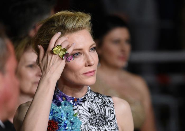 Cate Blanchett, chignon élégant, bagues avec papillons colorés, robe unique bariolée, imprimés floraux