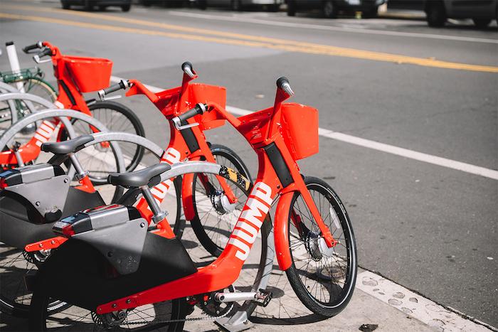 vélo uber en rouge et noir sur un trottoir, vélo libre service autonome développée par uber avec les avancées de la robotique