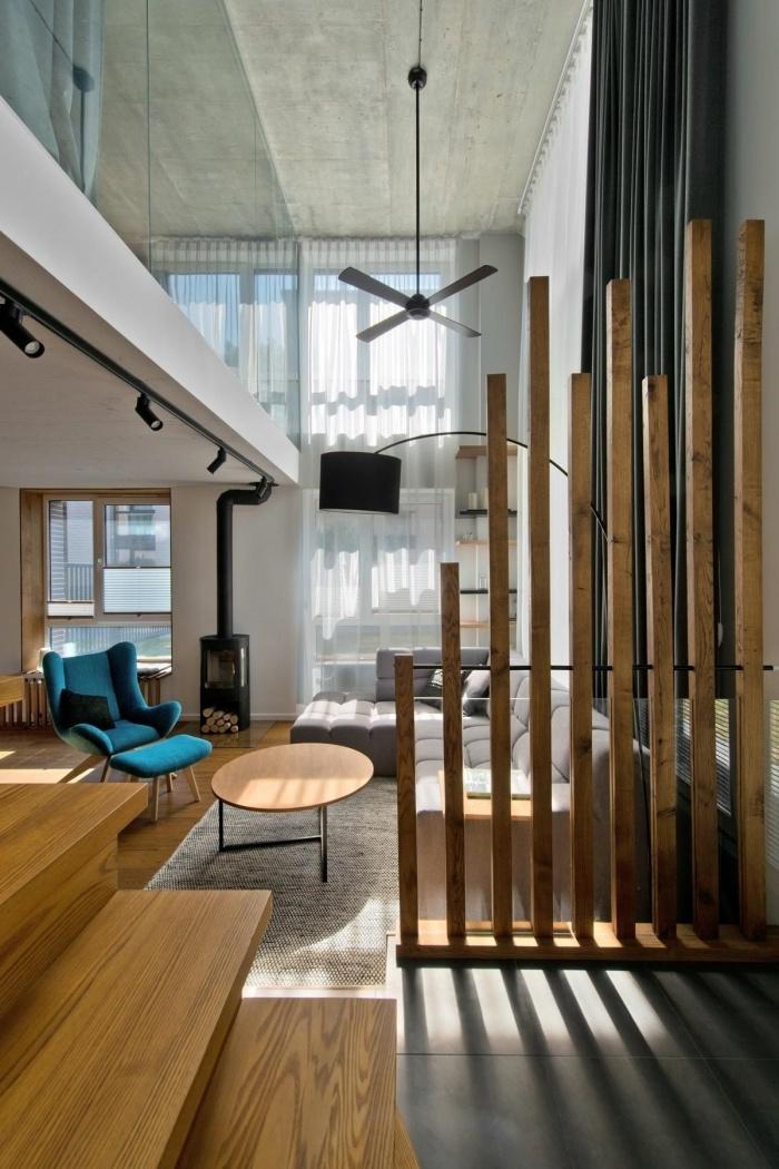 comment aménager un salon moderne loft aux murs blancs avec meubles en bois et une séparation pièce originale