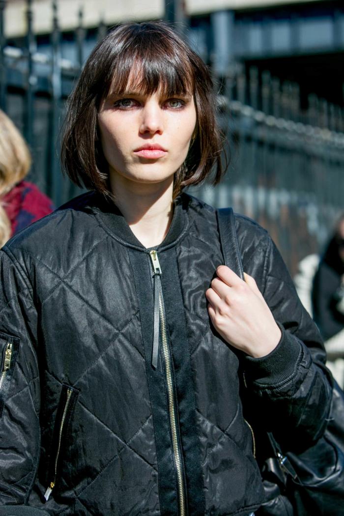 cheveux châtain lissés, coiffure carré femme; frange lisse, manteau noir matelassé, coupe carré plongeant