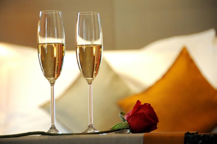 Boire de champagne ensemble, rose rouge, chambre d'hotel, lit et coussins, photo pour saint valentin romantique