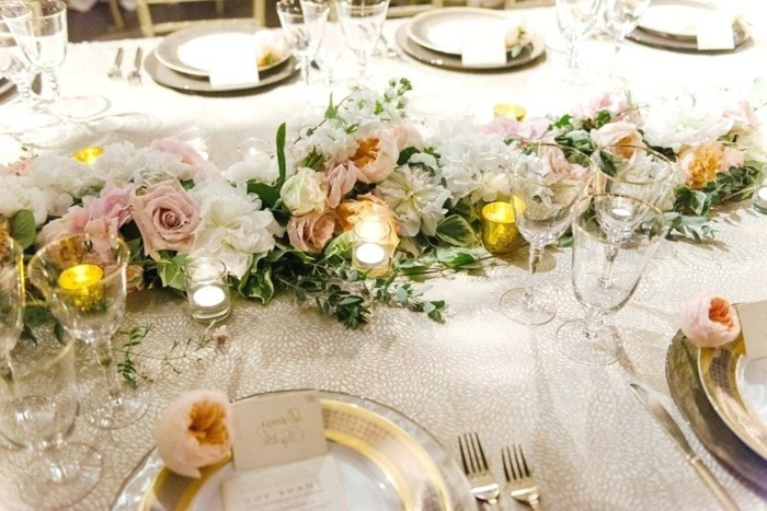 nappe de table de mariage blanche, assiettes aux rebords dorés, couronne de fleur comme centre de table de mariage