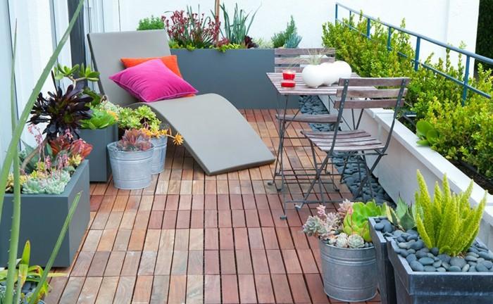 idee de decoration balcon en bois composite, chaise longue gris, table et chaises en bois et metal, bacs à fleurs et galets