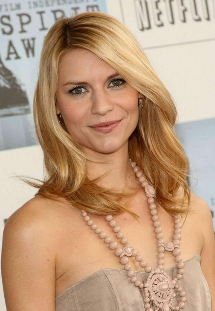raie asymétrique, longs cheveux blonds, robe élégante, collier en boules roses
