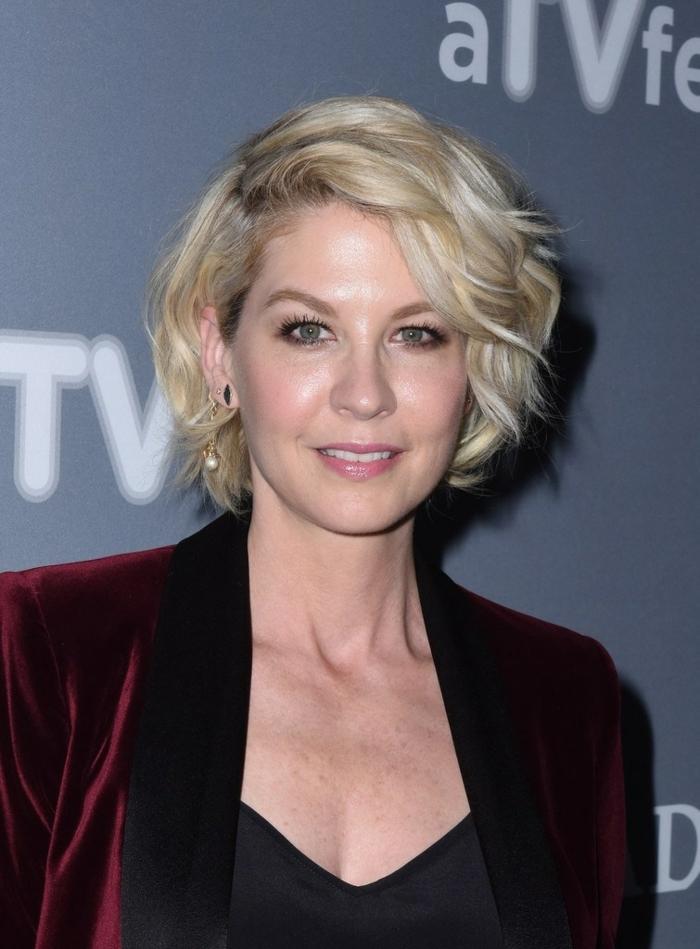 coupe de cheveux court femme 50 ans, cheveux blonds légèrement bouclés, maquillage smokey eye, veste burgundy