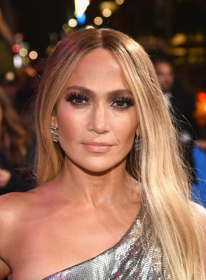 Jennifer Lopez, longs cheveux, lèvres couleur nude, robe asymétrique imitation peau de serpent