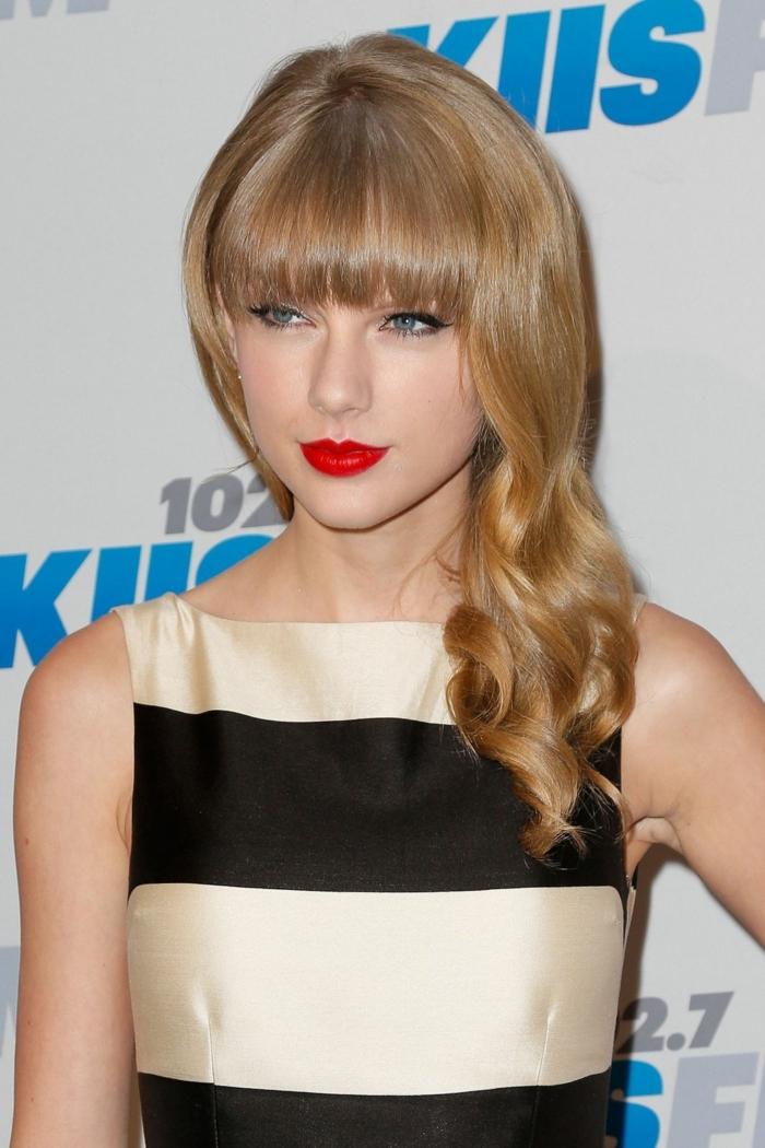 les cheveux de Taylor Swift, lèvres rouges, robe en noir et beige, cheveux bouclés blond miel