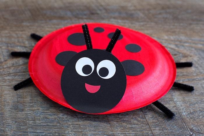 idée de recyclage d assiette jetable en papier rouge décoré de pois noirs et tête en cercle noir motif coccinelle avec antennes et pattes en cure pipe, activité manuelle printemps