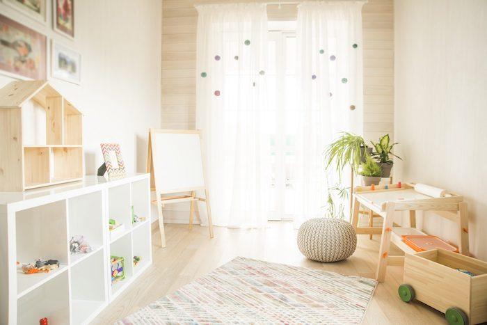 aire d activité avec des tableaux de jeu, pouf gris, coffre à jouets bois sur roulettes, parquet bois clair, etagere kallax blanche, rideau blanc à pompons colorés