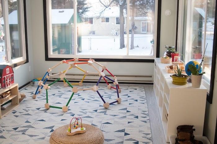 etagre kallax dans la chambre enfant pour ranger decorations et jouets, tapis d'éveil, pouf en jonc de mer, grandes fenetres