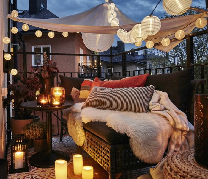 aménagement petit balcon romantique avec canapé décoré de plaid et coussins décoratifs, plusieurs bougeoirs et bougies, voile d ombrage et guirlande lumineuse boule