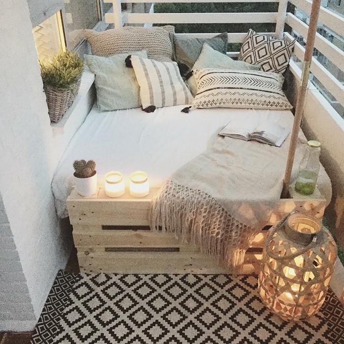 petit canapé lit en bois de palette avec matelas et coussins decoratifs gris et beige, tapis gris et noir, bougeoirs et bougies deco balcon