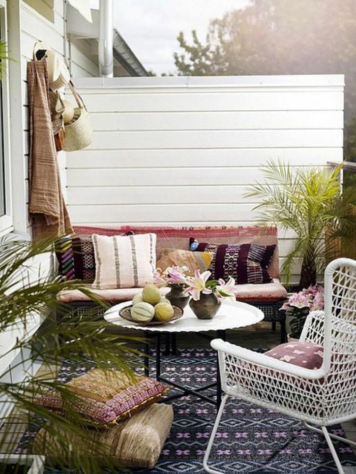 table basse ronde et chaise blanche en rotin petit canapé décoré de coussins, coussins d assise, brise vue bois blanchi, tapis noir à motifs orientaux
