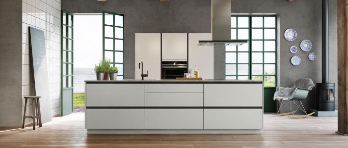 design contemporain dans une cuisine aux murs gris design béton, déco de cuisine ouverte avec îlot central en blanc et noir