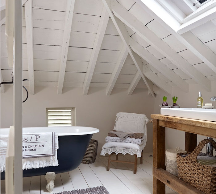 salle de bain mansardée sous plafond en bois blanchi, parquet bois blanchi, baignoire bleu nuit, lavabo blanc dans meuble salle de bain rustique