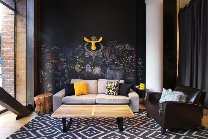 enduit à effet craie noir, déco de salon au parquet bois et murs foncés avec peinture à texture ardoise, accents jaune dans la déco