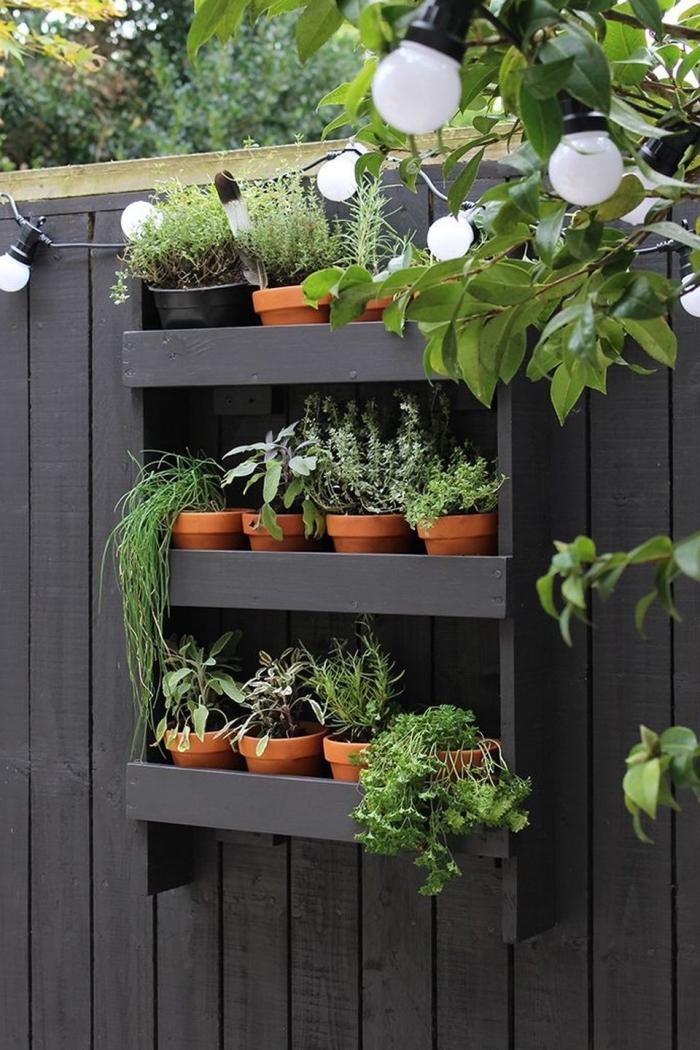 une palette recyclée en jardinière murale qui accueille plusieurs pots d'herbes aromatiques, palette jardinière verticale