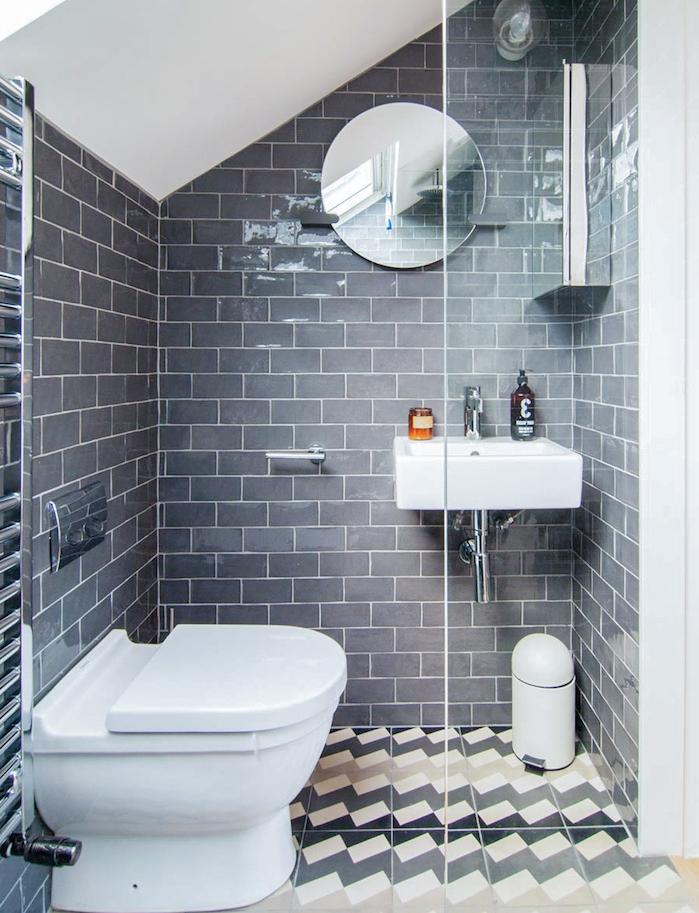 idée de douche sous pente en couleur grise dans une petite salle d eau avec wc blanc, miroir rond et paroi vitré