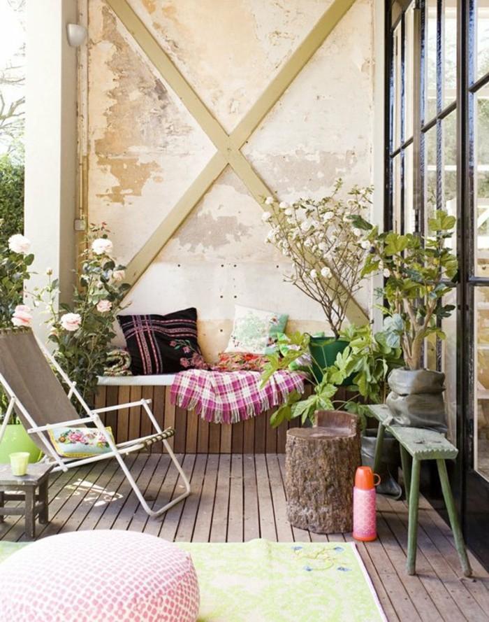aménagement terrasse avec petit banc contre un mur usé, chaise pliante, revetement sol en bois composite, tapis vert clair, coussins decoratifs, plantes fleuris pour balcon