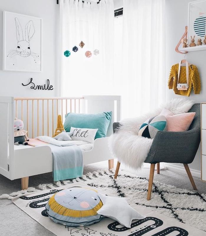 decoration chambre fille en blanc et pastel, rideaux blancs, lit à barreaux demi ouvert, tapis noir et blanc, fauteuil gris, coussins decoratifs enfant
