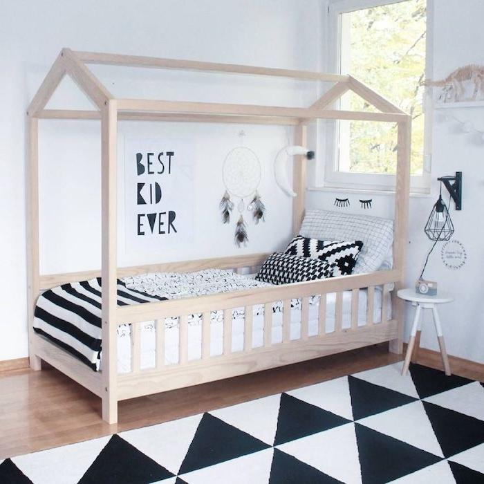 lit montessori en bois dans une chambre enfant scandinave en noir et blanc, chambre avec parquet, tapis noir et blanc à triangles