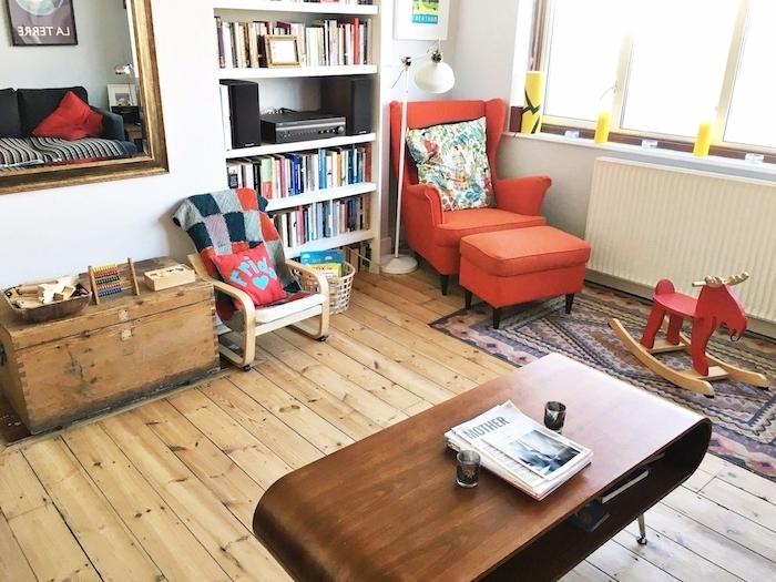 deco salon avec espace montessori prèss de la bibliothèque, fauteuil enfant et adulte, coffre rangement et table bas, cheval à bascule, table salon bois originale