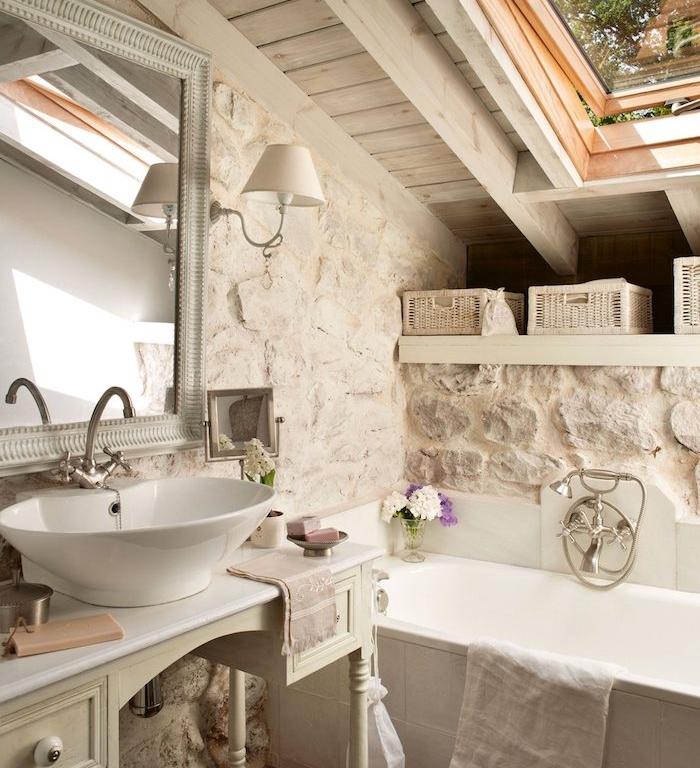 mur de pierres, baignoire blanche, lavabo à poser sur console meuble ancien salle de bain, miroir vintage, idee salle de bain rustique campagne chic