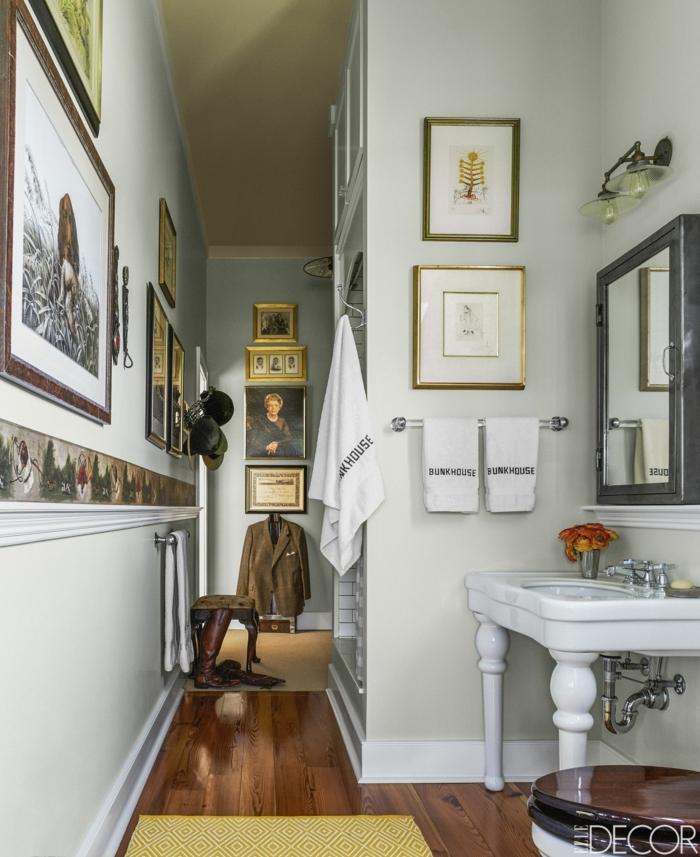 vasque pied blanche, sol en bois, plusieurs peintures encadrées, peinture toilette gris clair