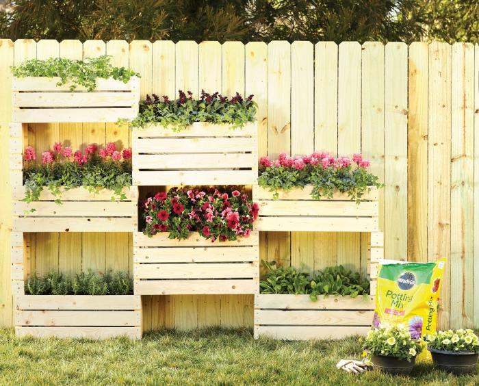 aménager un petit jardin en hauteur avec une structure en bois portant des bacs à planter fleuris