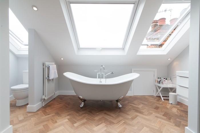 salle de bain sous pente simple avec une baignoire blanche sur un parquet, grosses fenetres, wc séparé