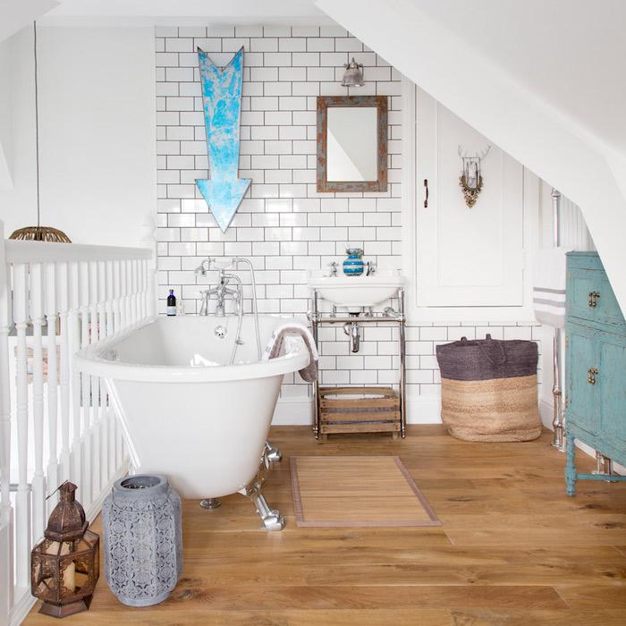 aménagement petite salle de bain mezzanine avec baignoire blanche sur parquet, meuble salle de bain bleu chine, lavabo console contre mur carrelage blanc
