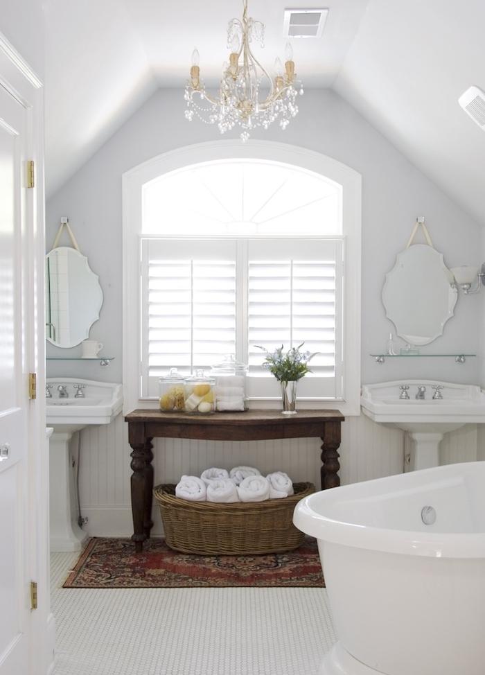 salle de bain blanche traditionnelle avec tapis oriental, petite table bois marron, baignoire blanche, miroirs vintage, lustre élégant