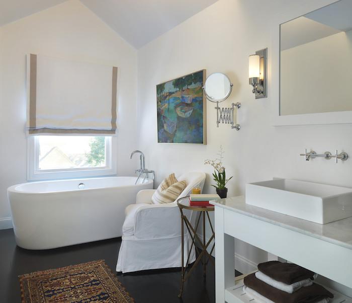 murs blancs avec tableau d art sur mur blanc, baignoire blanche sur sol gris foncé, miroir salle de bain, meuble blanc avec vasque, tapis oriental