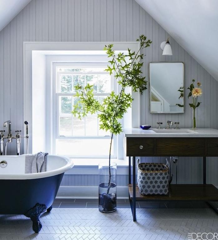 salle de bain avec baignoire bleu foncé, sol carrelage blanc, meuble ancien en bois avec plan de travail bois, plante verte branche dans vase, lambris gris clair