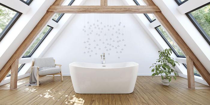 poutres apparentes et plusieurs fenêtres dans une salle de bain mansardée avec une baignoire design au centre