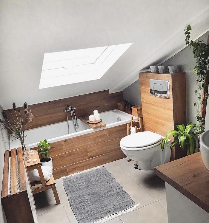 baignoire avec revetement de bois pour une touche rustique, wc suspendu, tapis gris sur carrelage gris, salle de bain zen, ambiance spa