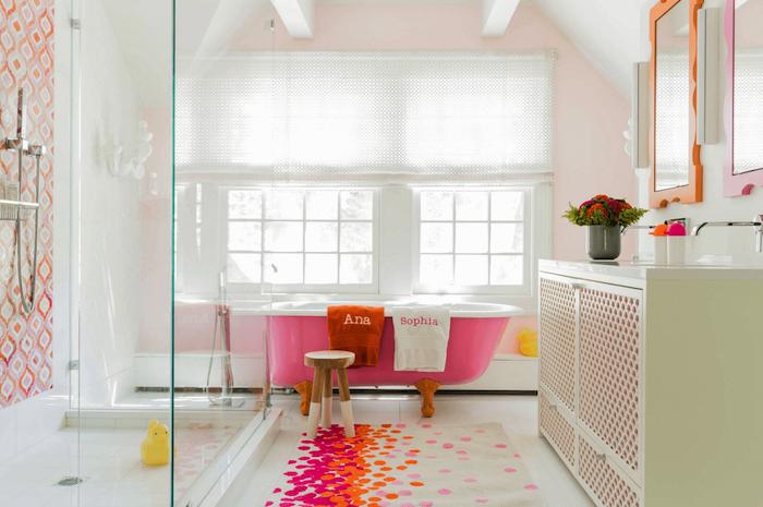 baignoire rose dans une salle de bain rose et blanc avec une cabine de douche vitrée et tapis coloré, amenagement sous pente original