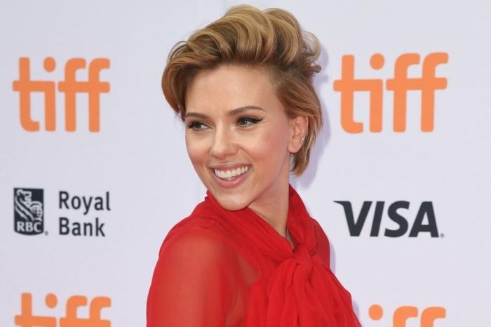 Scarlett en chemise rouge subtile, eyeliner noir, lèvres neutres, carré court, frange de coté