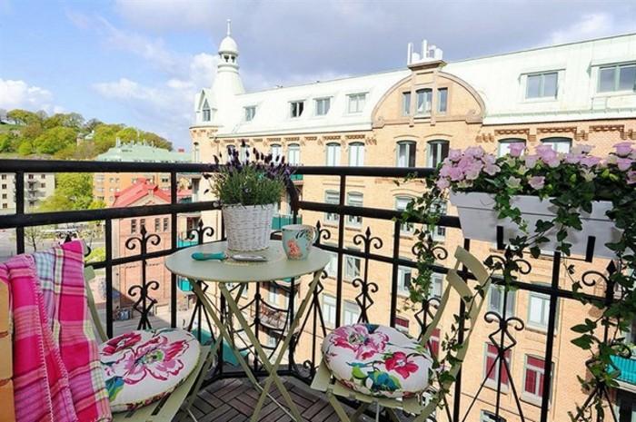 idée aménagement petit balcon fleuri avec des bacs et pots de fleur, chaises métalliques décorées de coussins à motifs fleuris