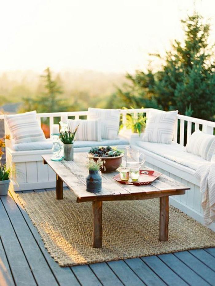 canapé d angle exterieur en bois blanc décoré à coussins blancs, terrasse bois composite gris, tapis beige, table basse rustique